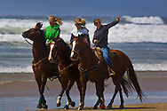 Three young women riding horses on the sand at Oceano State Beach, Oceano, California