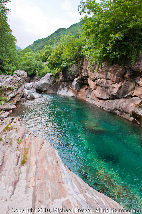 Beautiful aquamarine river pool surrounded by striated rocks and green forests on the Versasca River in Ticino, Switzerland.