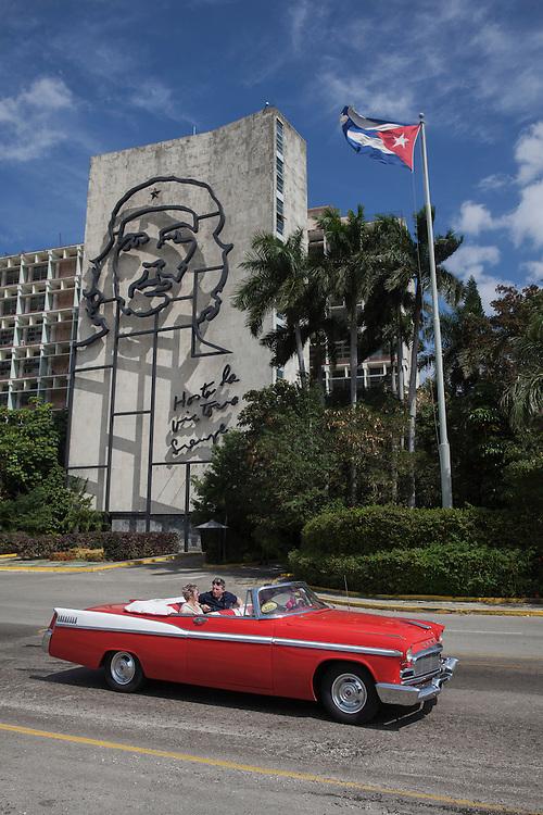 A tourists couple enjoys a ride in old American convertible at the Plaza de la Revolucion, next to a building wall illustrated with a drawing of 'Che' Guevara, in Havana, Cuba.<br /> <br /> Una pareja de turistas pasea en un coche antiguo americano descapotable por la Plaza de la Revoluci&oacute;n, junto a una pared de un edificio ilustrada con el rostro del Che Guevara.