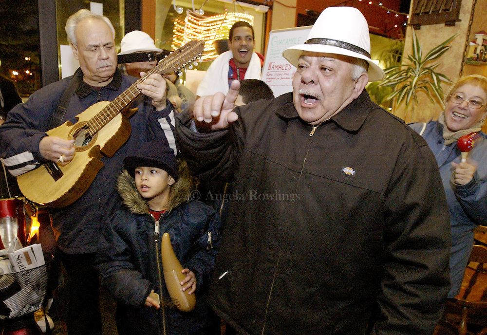 "12/08/05 Boston, MA-- Gregorio Nieves, left, plays the cuatro, Armani Martinez, 5, plays the quiro, and Paco Figueroa sings as they make their rounds during ""parrandas"" in the Villa Victoria neighborhood of the South End Thursday.  Parrandas are a part of Puerto Rican tradition where Christmas carolers stop at friends and neighbors' houses to sing and party.  (120805parrandasar02, saved in fri, Staff Photo by Angela Rowlings)"