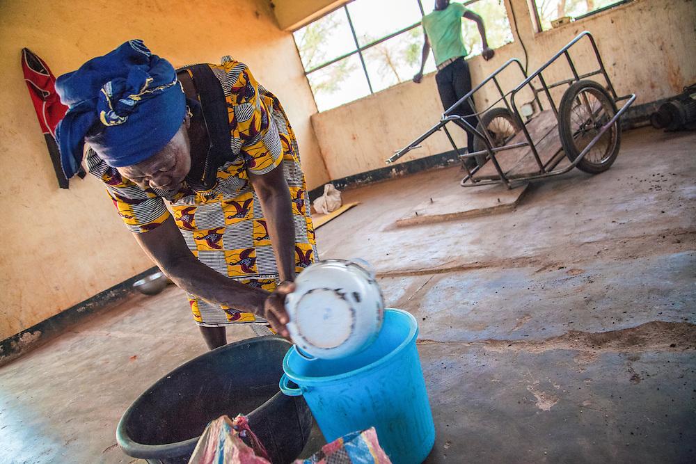 LÉGENDE: Une femme remplie un bassin de noix de Karité. LIEU: Centre COFEMAK, Koumra, Tchad. PERSONNE(S): Femme (à gauche) et homme (en arrière plan, droite).
