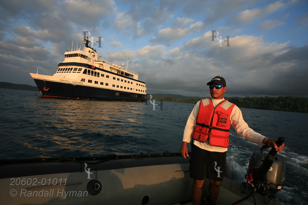 Crewman from Cruise West's ship, Pacific Explorer, pilots Zodiac in Drake Bay along Pacific Ocean's Osa Peninsula, Costa Rica.