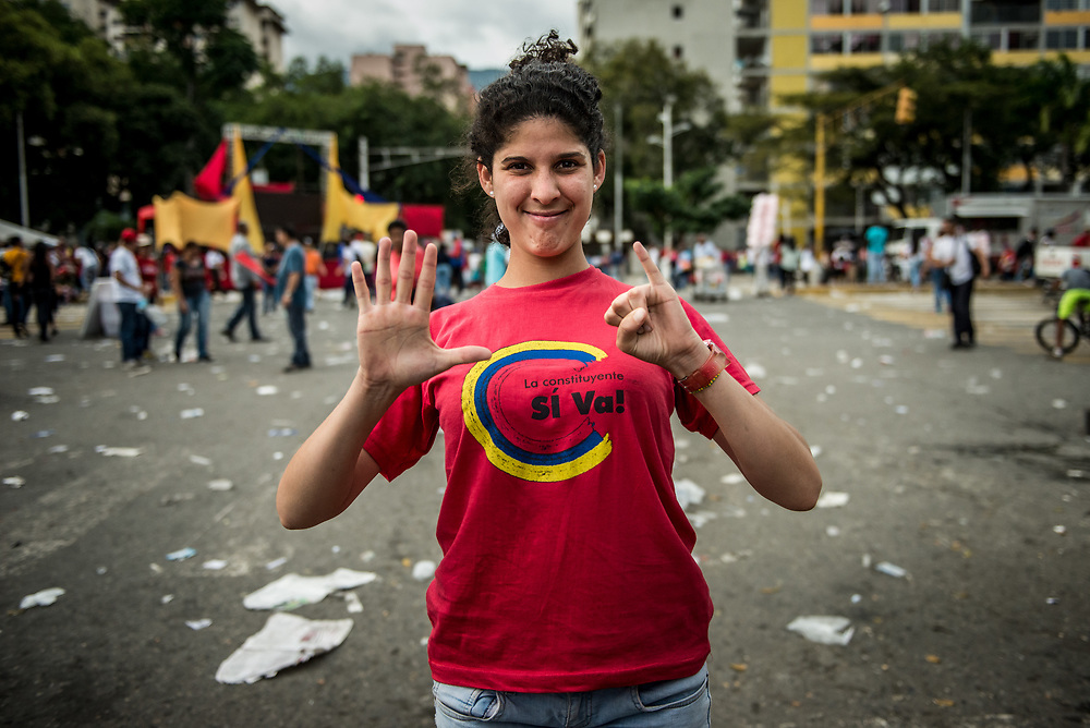 CARACAS, VENEZUELA - JULY 27, 2017: A government supporter poses for a portrait signaling her support for candiate number 6, at the final campaign rally for candidates for the election of the new constituent assembly, that will be held on July 30th. They marched and danced in the streets, as President Maduro and other socialist leaders addressed the large crowd. Opponents of the government criticize President Maduro for calling for this election - saying the new assembly is a power grab, and will be a puppet of the President - the only candidates on the ballot are government loyalists. Critics also fear the new assembly will re-write the constitution and wipe out the democratically elected and opposition controlled congress. There have been widespread reports of voter intimidation, and of the government threatening state workers and citizens that receive government benefits like subsidized food - who report the government telling them they are obligated to vote, and if they don't, they will lose their jobs and benefits. Thousands have taken to the streets to protest the election in the days leading up to the July 30th vote.  PHOTO: Meridith Kohut for The New York Times