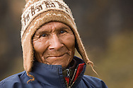 A local Aymara Indian smiles toward the camera in the mountains outside of Sorata, Bolivia