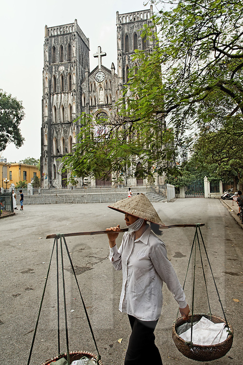 Street vendor wearing a conical hat carries a yoke on her shoulder as she walks past Saint Joseph Cathedral, Hanoi, Vietnam, Southeast Asia
