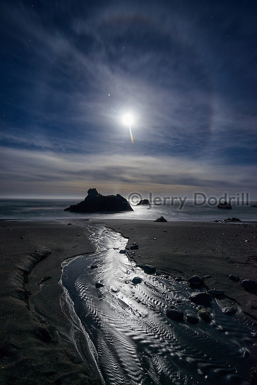 A halo circles the moon as it sets over the Pacific Ocean at Furlong Gulch, Sonoma Coast State Park near Bodega Bay, California