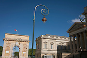 17th century Arc de Triomphe with Romanesque architecture of the Palais de Justice and retro street lighting in Montpellier, south of France.