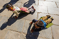 Tibetan children prostrating themselves repeatedly as they circumambulate through Barkhor Square and along The Barkhor (around the area of the Jokhang Temple), the most sacred temple in Tibet, Lhasa, Tibet, China.
