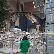 A passer by views an earthquake damaged building in Christchurch after a Powerful earth quake ripped through Christchurch, New Zealand on Tuesday lunch time killing at least 65 people as it brought down buildings, buckled roads and damaged churches and the Cities Cathedral. Photo Tim Clayton