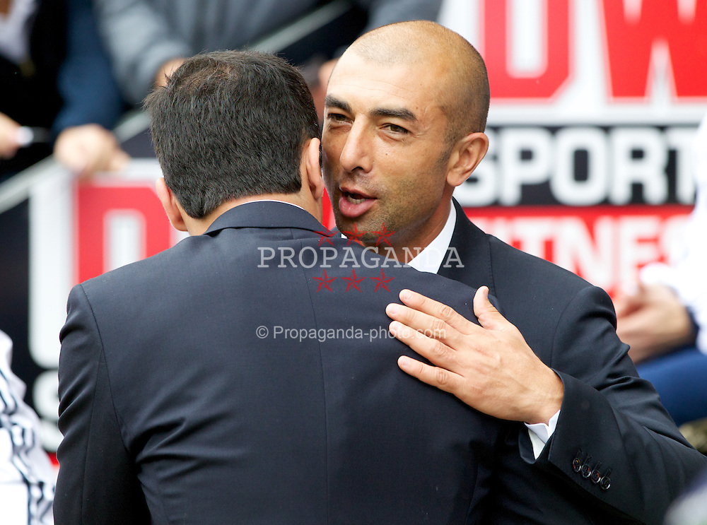 WIGAN, ENGLAND - Sunday, August 19, 2012: Chelsea's manager Roberto Di Matteo hugs Wigan Athletic's manager Roberto Martinez before the Premiership match at the DW Stadium. (Pic by Vegard Grott/Propaganda)