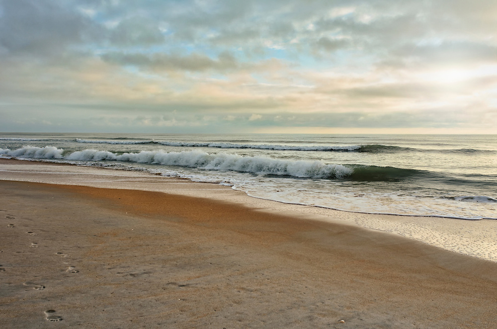 Beautiful sandy beach, dramatic sky, sun rays and rolling waves just after sunrise, Palm Coast, Florida, USA, September 2011.