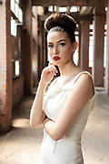 Fashion photo of model in 1950s hair and dress in abandoned building.