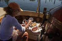 "Perfect timing for a lunch of kielbasa cooked in the wood fired copper plated firebox of the ""Phoenix"" with Kristie LeGates as chef and first mate after making the trek from Lees Mill, Moultonboro to 19 Mile Bay, Tuftonboro on Wednesday.  (Karen Bobotas/for the Laconia Daily Sun)"