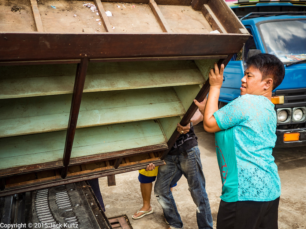 12 NOVEMBER 2015 - BANGKOK, THAILAND:  A woman loads a bookcase into a truck. She was helping her sister, who was being evicted from  Wat Kalayanmit, move. Fifty-four homes around Wat Kalayanamit, a historic Buddhist temple on the Chao Phraya River in the Thonburi section of Bangkok, are being razed and the residents evicted to make way for new development at the temple. The abbot of the temple said he was evicting the residents, who have lived on the temple grounds for generations, because their homes are unsafe and because he wants to improve the temple grounds. The evictions are a part of a Bangkok trend, especially along the Chao Phraya River and BTS light rail lines. Low income people are being evicted from their long time homes to make way for urban renewal.       PHOTO BY JACK KURTZ