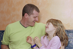 Father sitting at home on sofa with young daughter,