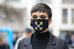© Licensed to London News Pictures. 14/02/2020. London, UK. A fashion enthusiast wearing a fashionable face mask arrives for the London Fashion Week shows in The Strand. The latest Coronavirus patient in London is linked to 'super spreader' attended transport conference with 250 people in Westminster. Photo credit: Dinendra Haria/LNP