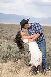 cowboy and a beautiful girl dancing outdoors overlooking a mountain range
