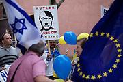 Frankfurt am Main | 05 July 2014<br /> <br /> Am Samstag (05.07.2014) demonstrierten am Domplatz in Frankfurt am Main etwa 25 Menschen f&uuml;r die Unabh&auml;ngigkeit der Ukraine und gegen den Einfluss von Russland.<br /> Hier: Demonstranten mit einem Plakat mit einer Grafik, in der Putin als Hitler stilisiert wird und der Aufschrift &quot;Putler - Hands Off Ukraine&quot;, links eine Flagge von Israel.<br /> <br /> [Foto honorarpflichtig, kein Model Release]<br /> <br /> &copy;peter-juelich.com