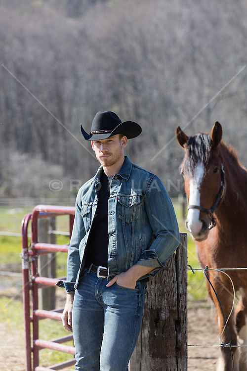 handsome All American cowboy on a ranch with a horse