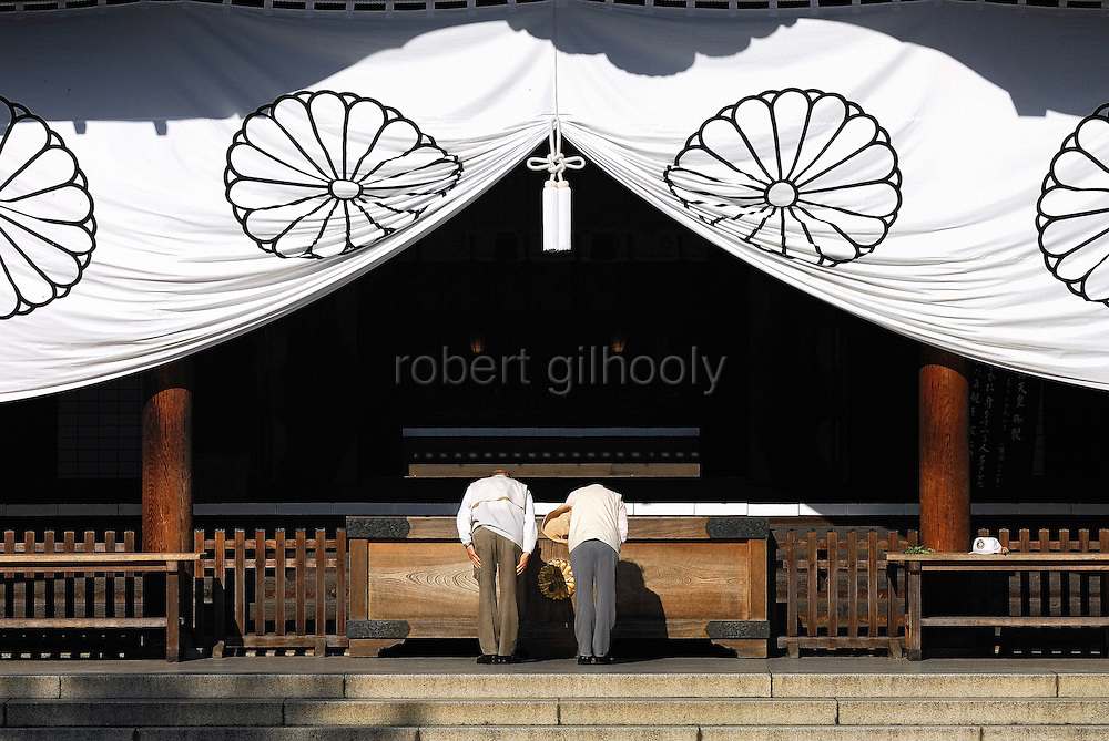 A couple bows during prayer at the main hall of Yasukuni Shrine in Tokyo, Japan. Every year on August 15, the day Japan officially surrendered in WWII, tens of thousands of Japanese visit the controversial shrine to pay their respects to the 2.46 million war dead enshrined there, the majority of which are soldiers and others killed in WWII and including 14 Class A convicted war criminals, such as Japan's war-time prime minister Hideki Tojo. Each year speculation escalates as to whether the country's political leaders will visit the shrine, the last to do so being Junichiro Koizumi in 2005. Nationalism in Japan is reportedly on the rise, while sentiment against the nation by countries that suffered from Japan's wartime brutality, such as China, has been further aggravated by Japan's insistence on glossing over its wartime atrocities in school text books...Photographer:Robert Gilhooly..