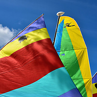Colorful Sailboat Sails at Half Moon Cay, Bahamas <br /> On Half Moon Cay, the phrase &ldquo;whatever sails your boat&rdquo; is inverted into &ldquo;whatever boat you sail&rdquo; because you can virtually rent any type of watercraft to enjoy your day on a sheltered lagoon.  Among your choices are these Sunfish sailboats or Hobie Cat catamarans.  Also available are kayaks, water bikes, paddle boats, jet skis or a simple float.
