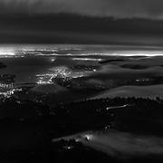 The San Francisco Bay Area shines in the night as coastal fog moves overhead. As seen from the summit of Mount Tamilpais in Marin County.