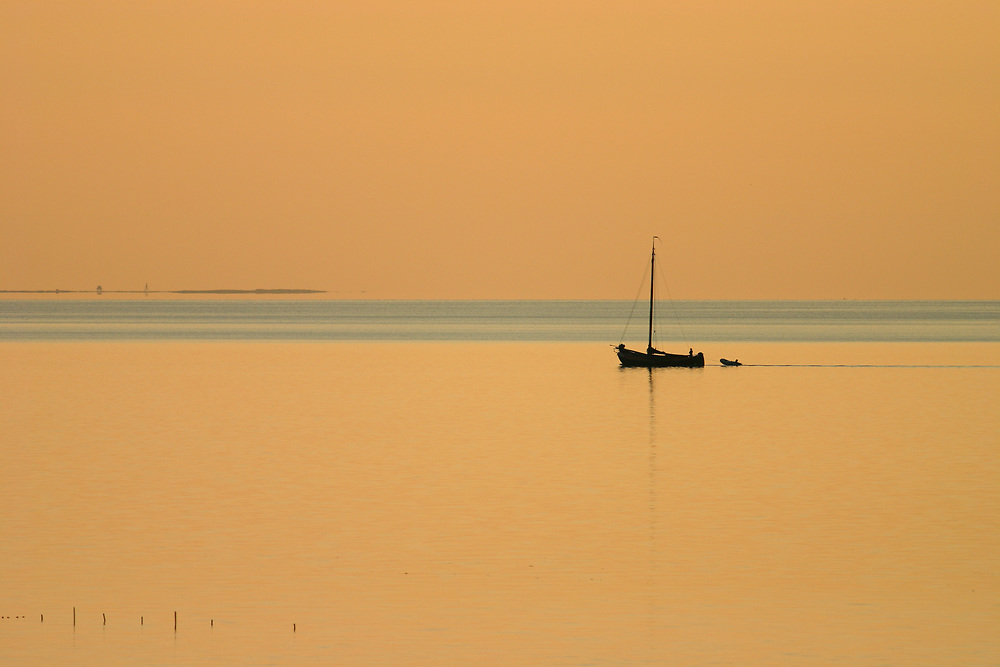 The sun is setting in the Waddenzee on a still evening. A small boat is sailing towards the harbour. In the background the small island of Griend is visible // De zon gaat onder in de Waddenzee. Een eenzaam bootje vaart op de motor richting de haven, het is vrijwel windstil. Op de achtergrond het vogeleiland Griend.