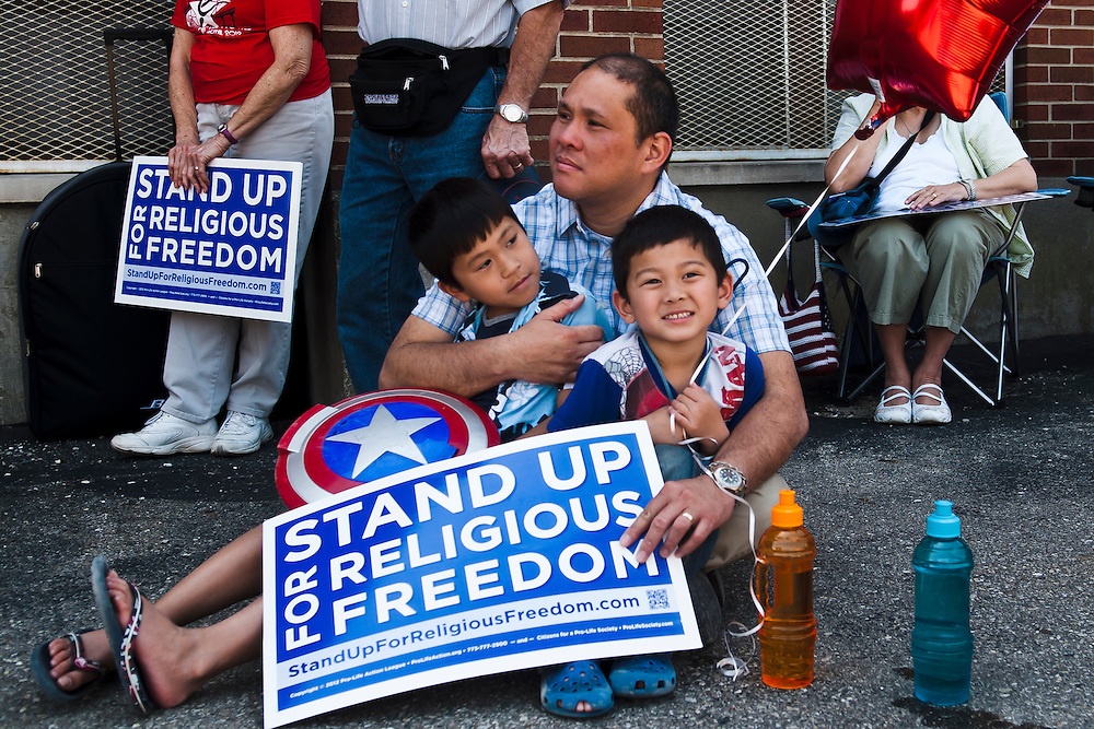Lathan Goumas | MLive.com..Raffy Urgino, of Swartz Creek, sits on the ground holding his sons Joey,7, and Pax, 6, during a protest rally at St. Matthew's Roman Catholic Church in Flint, Mich. on Friday June 8, 2012. Hundreds gathered at the church to protest a healthcare policy of the Obama administration they believe forces religious institutions to pay for health services that contradict their beliefs. After a rally at the church protestors marched to the federal courthouse in downtown Flint.