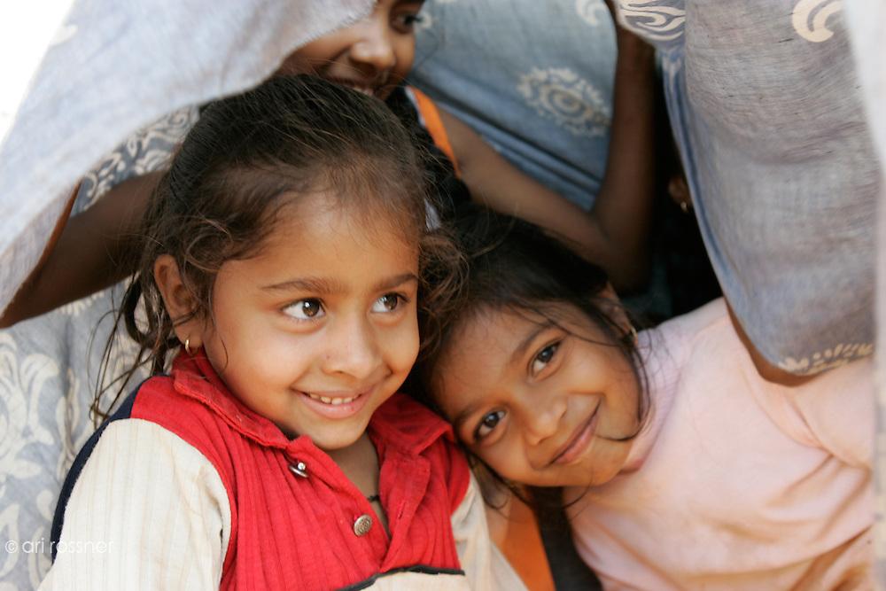 Three little girls who are hidden under a sari