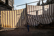 A boy is seen playng in the streets of Shejaiya, one of the most destroied district in the gaza streep. Two blankets are replacing the front walls of a house