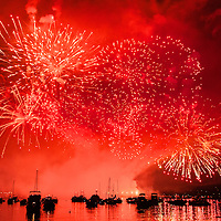Fireworks and boats in the ocean against a red sky
