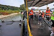 Nederland, Arnhem, 3-10-2011Het veerpontje de Samenwerking twee vaart tussen de zuidelijke rijnoever en de Westerbouwing heen en weer met fietsers en voetgangers. Het fietspontje wordt voortgestuwd door elektriciteit, zonneenergie, van de zonnepanelen op het dak. Groene stroom van Nuon.Sinds kort doet het ook dienst als leer werkproject voor werkloze jongeren. Een klas schoolkinderen steekt de rivier over tijdens een fietstocht.Foto: Flip Franssen/Hollandse HoogteFoto: Flip Franssen