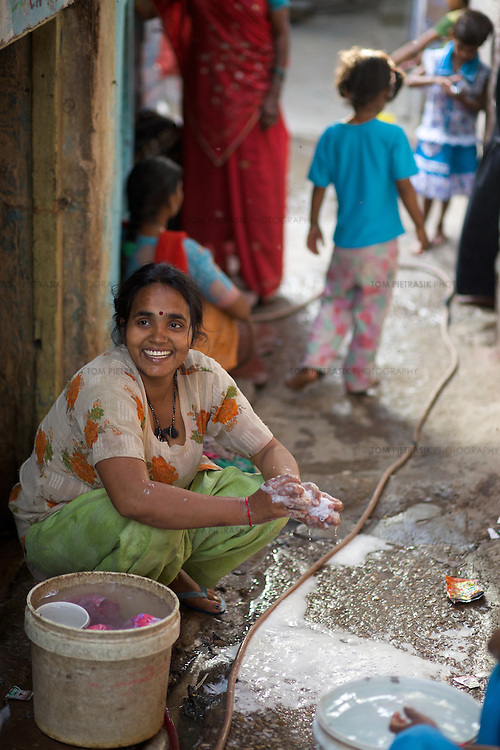 A woman washes clothes outside her home in a Delhi slum. ..Photo: Tom Pietrasik.Delhi, India.April 14th 2010