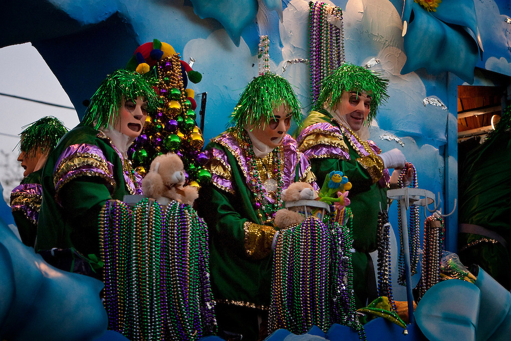 Masked Krewe riders on Mardi Gras floats throw beads, doubloons and other trinkets to the crowds of people during Carnival Season as they roll through the Uptown area of New Orleans, Louisiana, USA.