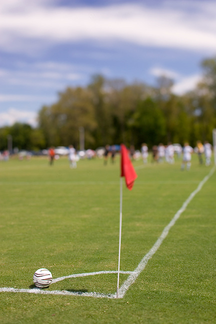 Corner kick area of a soccer field with flag and game action in the background