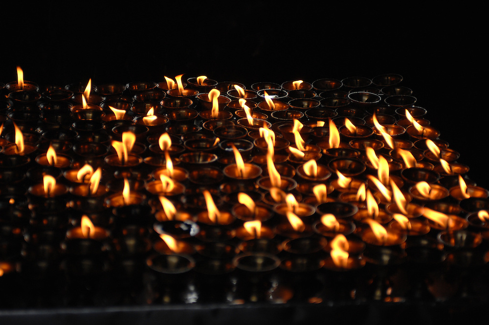 Prayer candles flickering inside a Buddhist temple at Swayambhunath in Nepal.