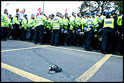 A lost shoe lays on the road as police officers push back hundreds of EDL supporters during the protest against what they see as the influence of Islam in the Tower Hamlets area of London, United Kingdom. Saturday, 7th September 2013. Picture by Piero Cruciatti / i-Images