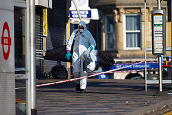 A forensics investigator removes bags from the spot where a man alleged by witnesses to be a drug dealer was stabbed to death outside Ilford Station following a fight outside a Paddy Power betting shop 100 yards away on Ilford High Road. London, February 27 2019.