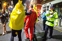 © Licensed to London News Pictures . 26/12/2017. Wigan, UK. A real policeman amongst fancy dress wearing party-goers . Revellers in Wigan enjoy Boxing Day drinks and clubbing in Wigan Wallgate . In recent years a tradition has been established in which people go out wearing fancy-dress costumes on Boxing Day night . Photo credit: Joel Goodman/LNP