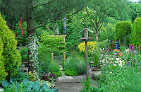 large well planted garden with lots of foliage and bird feeder