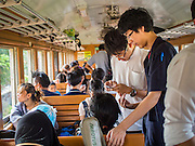 20 MARCH 2015 - PRACHINBURI, PRACHINBURI, THAILAND: Thai teenagers check their smart phones on a third class train leaving Chachoengsao station going towards Bangkok. The State Railways of Thailand (SRT), established in 1890, operates 4,043 kilometers of meter gauge track that reaches most parts of Thailand. Much of the track and many of the trains are poorly maintained and trains frequently run late. Accidents and mishaps are also commonplace. Successive governments, including the current military government, have promised to upgrade rail services. The military government has signed contracts with China to upgrade rail lines and bring high speed rail to Thailand. Japan has also expressed an interest in working on the Thai train system. Third class train travel is very inexpensive. Many lines are free for Thai citizens and even lines that aren't free are only a few Baht. Many third class tickets are under the equivalent of a dollar. Third class cars are not air-conditioned.   PHOTO BY JACK KURTZ