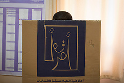 © Licensed to London News Pictures. 30/04/2014. Sulaimaniya, Iraq. An Iraqi-Kurdish man casts his vote behind a cardboard booth located in a school during the 2014 Iraqi parliamentary elections in Sulaimaniya, Iraqi-Kurdistan today (30/04/2014). <br /> <br /> The period leading up to the elections, the fourth held since the 2003 coalition forces invasion, has already seen polling stations in central Iraq hit by suicide bombers causing at least 27 deaths. Photo credit: Matt Cetti-Roberts/LNP