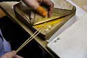 Kanazawa, March 16 2015 - Demonstration of paper insertion, part of gold leaf traditional process in the main shop of Hakuza, a  gold leaf maker and seller. 99% of gold leaves made in Japan are made in Kanazawa.
