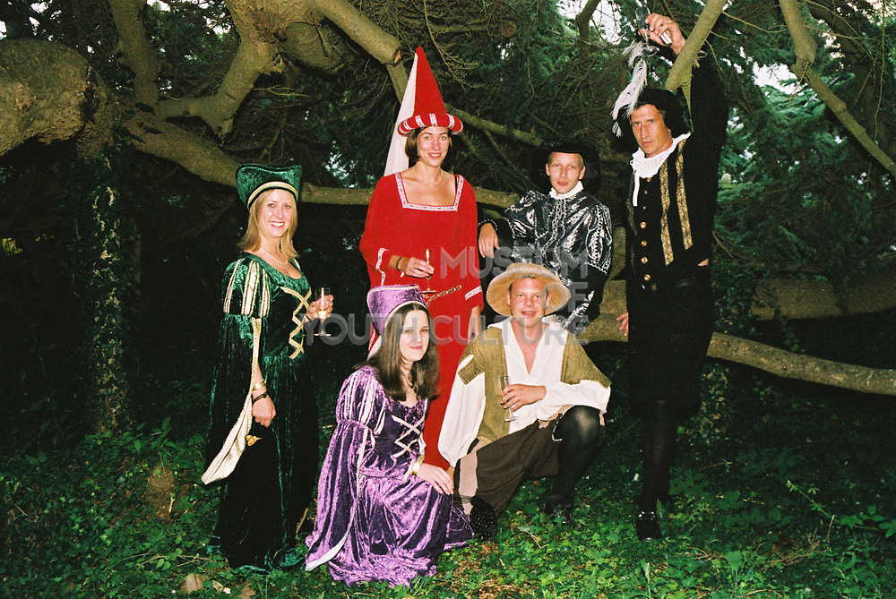 Group wearing historical fancy dress costumes posing beside a tree in the gardens at Posh, Addington Palace, UK, August, 2004