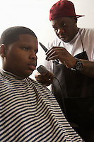 Boy with head being shaved in the barbers