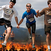/Andrew Foulk/ For The Californian/ .A group of competitors hold hands as they jump over the fire pit during the Warrior Dash 5K race in Lake Elsinore Sunday.