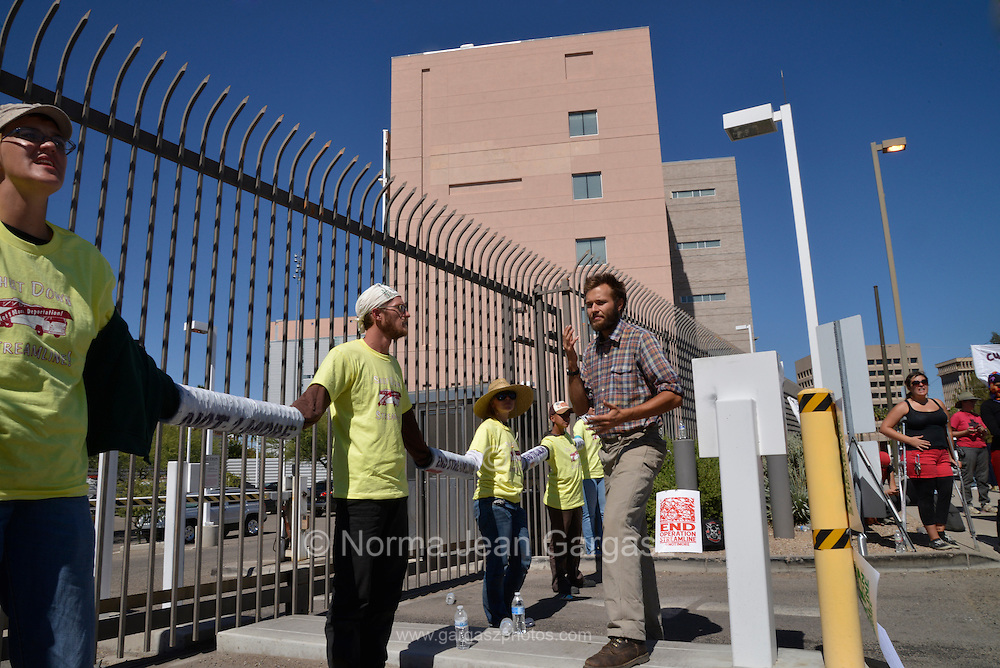 Protesters block the entrance to the federal courthouse in protest of Operation Streamline on October 11, 2013, in Tucson, Arizona, USA, to prevent a bus carrying undocumented migrants from entering the facility for an immigration and deportation hearing.  The program instituted by the federal government expedites group hearings and deportation for those apprehended entering the United States illegally.