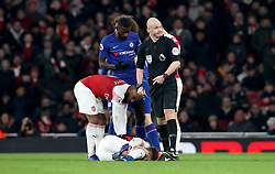 Arsenal's Alexandre Lacazette (left) tends to Arsenal's Aaron Ramsey as he lies injured on the pitch during the game