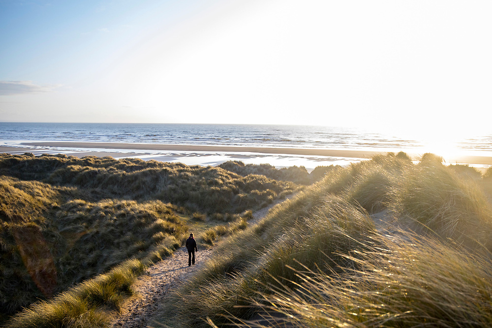 YNYSLAS, WALES, UK 16TH MARCH 2020 - Person walking through the Dyfi National Nature Reserve sand dunes during sunset sunlight, Borth and Ynyslas Beach and Dyfi Estuary, County of Ceredigion, Mid Wales, UK.