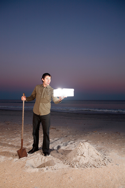 Wrightsville Beach, North Carolina - March 18: Davis McCeiver stands with a glowing box over a hole in the ground at the beach during sunset in Wrightsville Beach, North Carolina, on March 18, 2007.